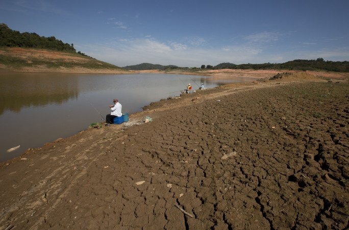Fisherman sit on parched land at the Jaguari dam in Branganca Paulista, Brazil on May 14, 2014. The dam is part of the Cantareira System, which is responsible for providing water to the Sao Paulo metropolitan area. The worst drought in more than 80 years is hitting Sao Paulo, Brazil's largest city, just as it prepares for the tens of thousands of foreigners expected at the World Cup opener. (AP Photo/Andre Penner)