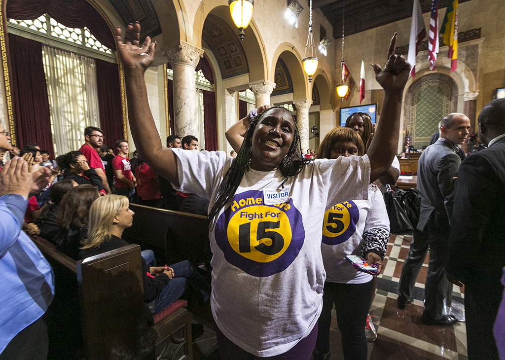 Workers react as the Los Angeles City Council votes 13-1 to raise the minimum wage to $15 an hour by 2020, but a second vote is required for final approval because the tally was not unanimous, in Los Angeles, Wednesday, June 3, 2015. Nonetheless, Council President Herb Wesson stressed to the cheering crowd that the outcome was all but certain. (AP Photo/Damian Dovarganes )