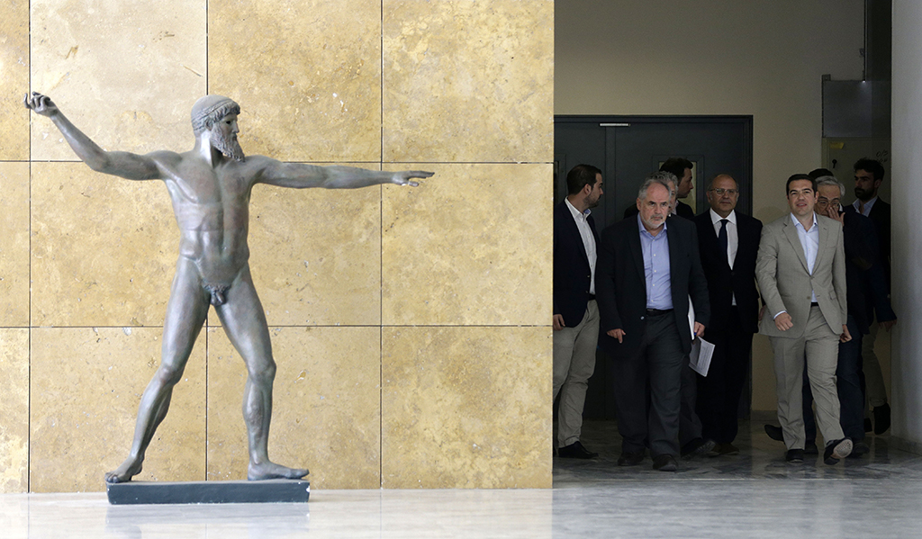 Greece's Prime Minister Alexis Tsipras, right, is accompanied by officials during his visit at the Education Ministry in Athens, Tuesday, June 2, 2015. Tsipras says Greece has submitted a proposal for an agreement with its creditors, as Athens seeks a deal that will to unlock desperately needed rescue money. (AP Photo/Thanassis Stavrakis)