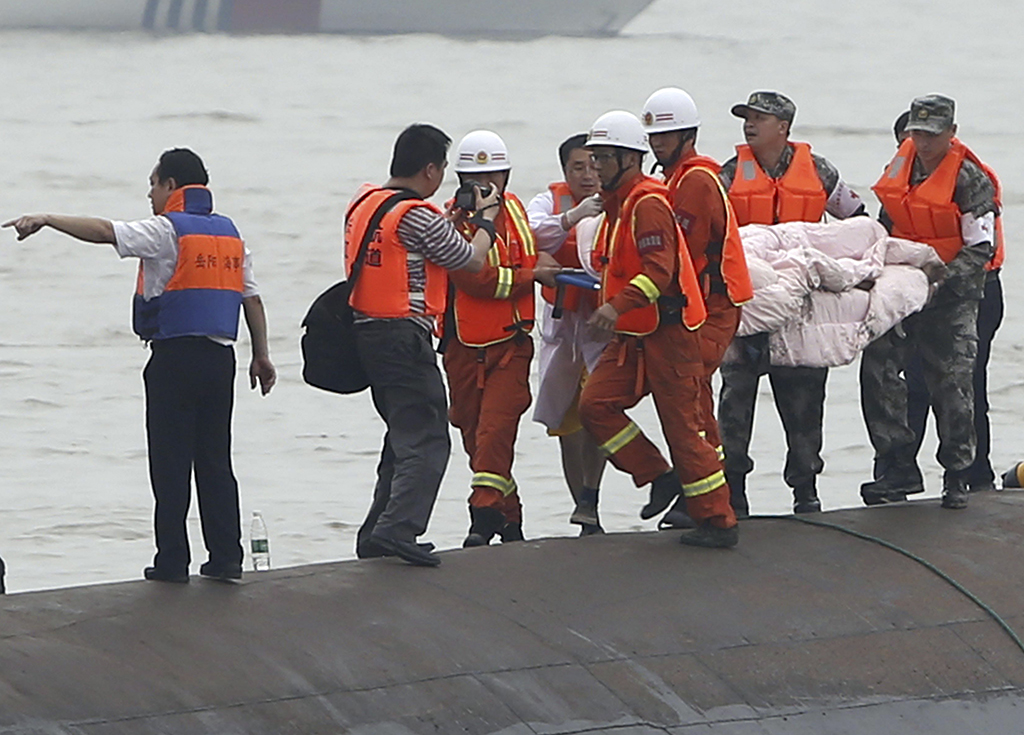 Rescuers carry a survivor pulled from the capsized cruise ship on the Yangtze River in Jianli in central China's Hubei province Tuesday June 2, 2015.  Divers on Tuesday pulled survivors from inside the overturned cruise ship, state media said, giving some small hope to an apparently massive tragedy with well over 400 people still missing on the river. (Chinatopix Via AP)