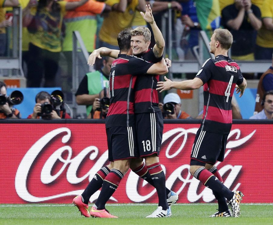 In this July 8, 2014 photo, Germany's Toni Kroos, centre,  celebrates after scoring his side's third goal during the World Cup semifinal soccer match between Brazil and Germany near a Coca-Cola advertisement at the Mineirao Stadium in Belo Horizonte, Brazil. With billions of dollars at stake and few other ways to tap into the global love of soccer, FIFA sponsors like Adidas, Coke and McDonald's are in the tricky position of wanting to preserve their investment while avoiding being tainted by the corruption scandal that's threatening soccer's global governing body. (AP Photo/Matthias Schrader, File)