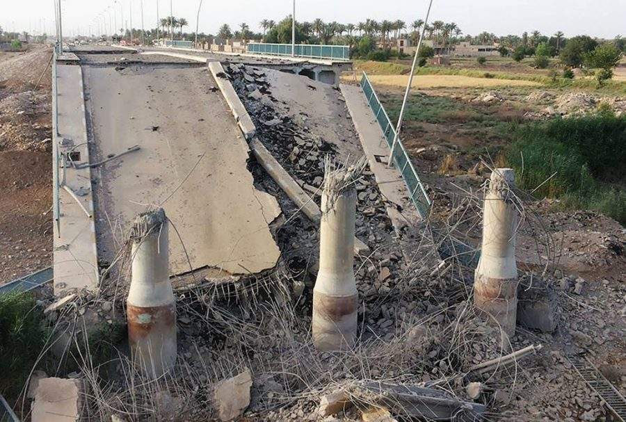 This photo taken Wednesday, June 3, 2015, shows a destroyed bridge on the Euphrates river in northern Ramadi, Iraq. The Islamic State group destroyed the bridge with a car bomb to cut the northern entrance to the city, locals said. (AP Photo)
