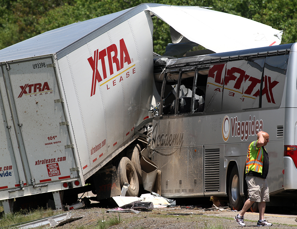 A man walks near the scene of a fatal collision between a tractor-trailer and a tour bus on Interstate 380 near Tobyhanna, Pa. Multiple people were killed and more than a dozen were sent to hospitals. (Jake Danna Stevens/The Times & Tribune via AP)