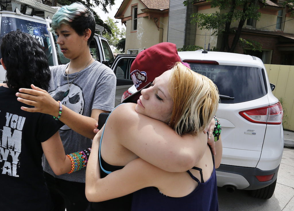 Ciera Rogers, far right, receives condolences from her friend Sam Hinde, on the loss of Rogers' grandfather, who was shot and killed the night before on a sidewalk near his home, in the northern Colorado town of Loveland, Thursday, June 4, 2015. At left, facing, Emmett Pelissier hugs Ciera Rogers' sister Sadie. (AP Photo/Brennan Linsley)