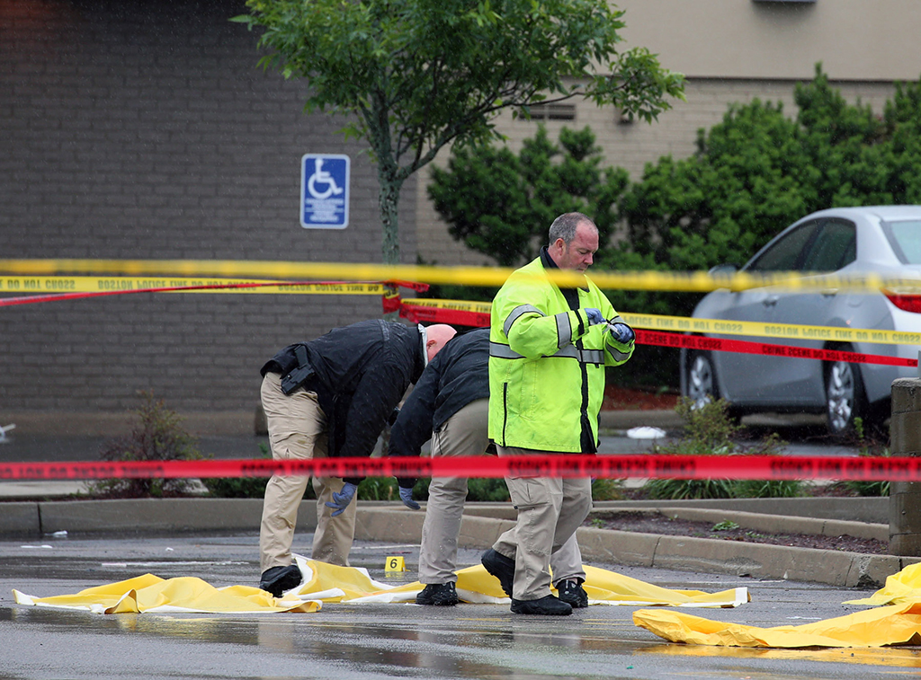 Boston police officers and detectives investigate at the scene of a shooting Tuesday morning, June 2, 2015) at 4600 Washington St. in Roslindale, Mass. A man under surveillance by terrorism investigators has been shot and killed by a Boston police officer. Police Commissioner William Evans confirmed from the scene that the man shot at about 7 a.m. at a pharmacy in the city's Roslindale neighborhood has died. Evans said the man was under surveillance by the Joint Terrorism task Force.  (Mark Garfinkel/The Boston Herald via AP)