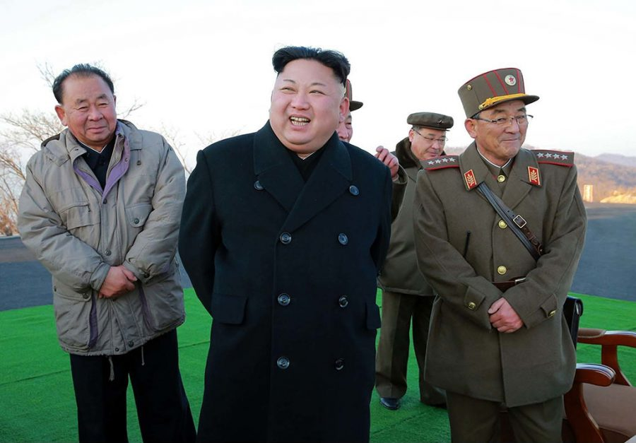 In this photo distributed by the North Korean government, leader Kim Jong Un smiles at an observation post to watch the launching of Scud missiles in Tongchang-ri in North Pyongan Province, North Korea.