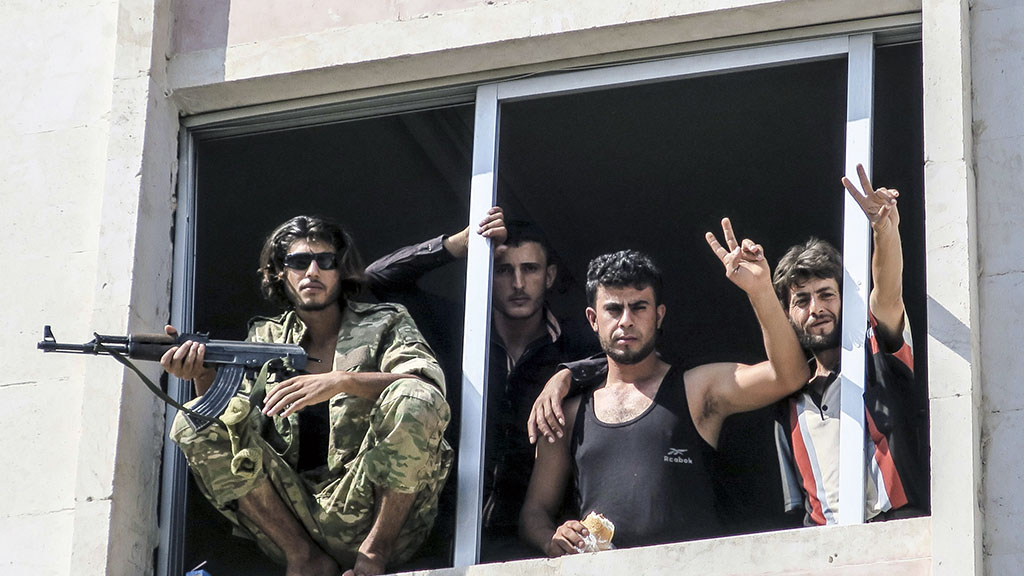 <p>Free Syrian Army fighters give the victory sign, in Jarablus, Syria. Veteran Syrian rebels who have fought Assad for years are struggling to find a place in a bewildering battlefield where several wars are all being waged at once by international powers. Battered by defeats, they bounce from alliance to alliance, feeling abandoned by the U.S. and faced with choosing whether to ally with Turkey or al-Qaida. (AP Photo, File)</p>