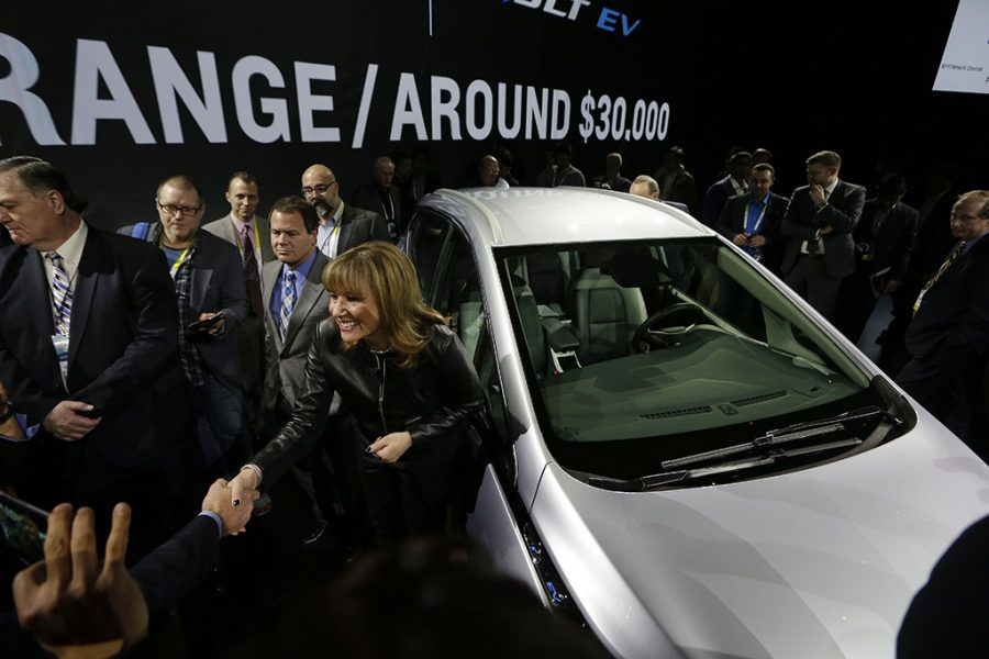 General Motors Co. CEO Mary Barra stands next to the Chevrolet Bolt EV electric car at CES International in Las Vegas. Tesla and General Motors have a budding rivalry that could help determine whether Detroit or Silicon Valley sets the course for the future of the auto industry. Right now Wall Street is favoring the upstart led by flamboyant Elon Musk to the established icon headed by the more restrained Mary Barra. (AP Photo/Gregory Bull, File)