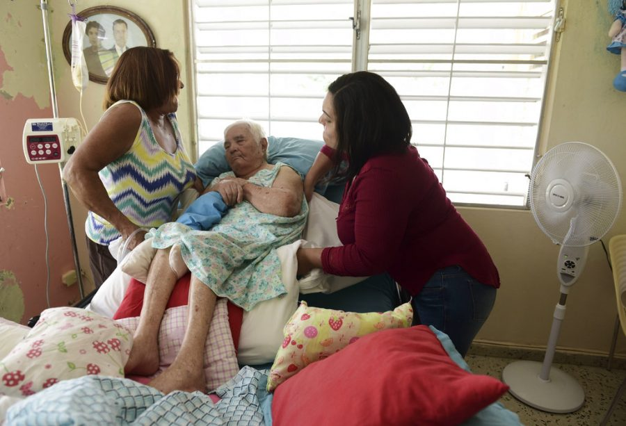 Norma Medina and a caregiver move her elderly mother