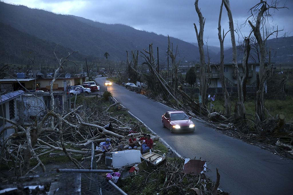 Neighbors sit on a couch outside their destroyed homes as sun sets in the aftermath of Hurricane Maria, in Yabucoa, Puerto Rico.