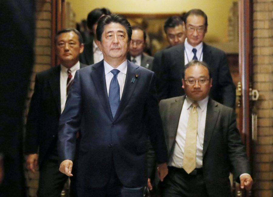Japanese Prime Minister Shinzo Abe goes to meet journalists after a phone call with the U.S. president.