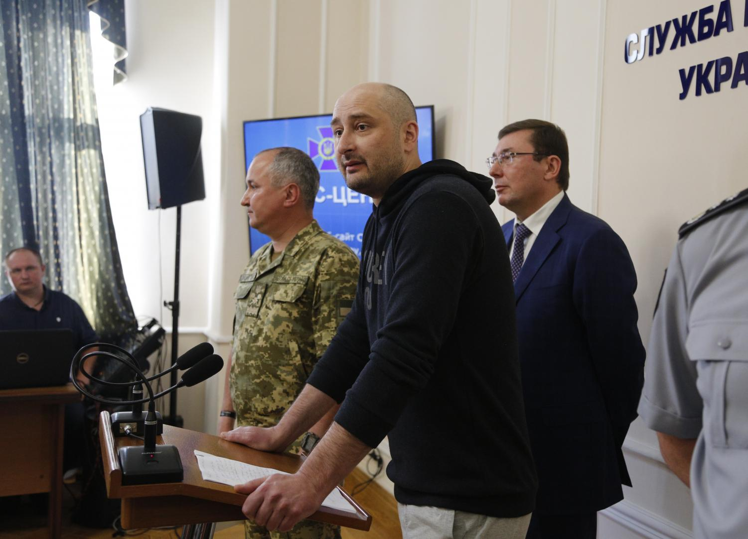 Russian journalist Arkady Babchenko, center, speaks to the media at the Ukrainian Security Service on Wednesday. Babchenko turned up at a news conference in the Ukrainian capital Wednesday less than 24 hours after police reported he had been shot and killed at his Kiev apartment building. The country's security services said Babchenko's death was faked to foil a plot to take his life.