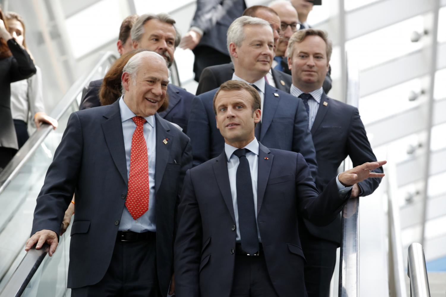French President Emmanuel Macron, right, and OECD Secretary-General Angel Gurria arrive at a meeting in Paris on Wednesday. Macron warned against trade wars in an impassioned speech about international cooperation two days before the Trump administration decides whether to hit Europe with new tariffs.