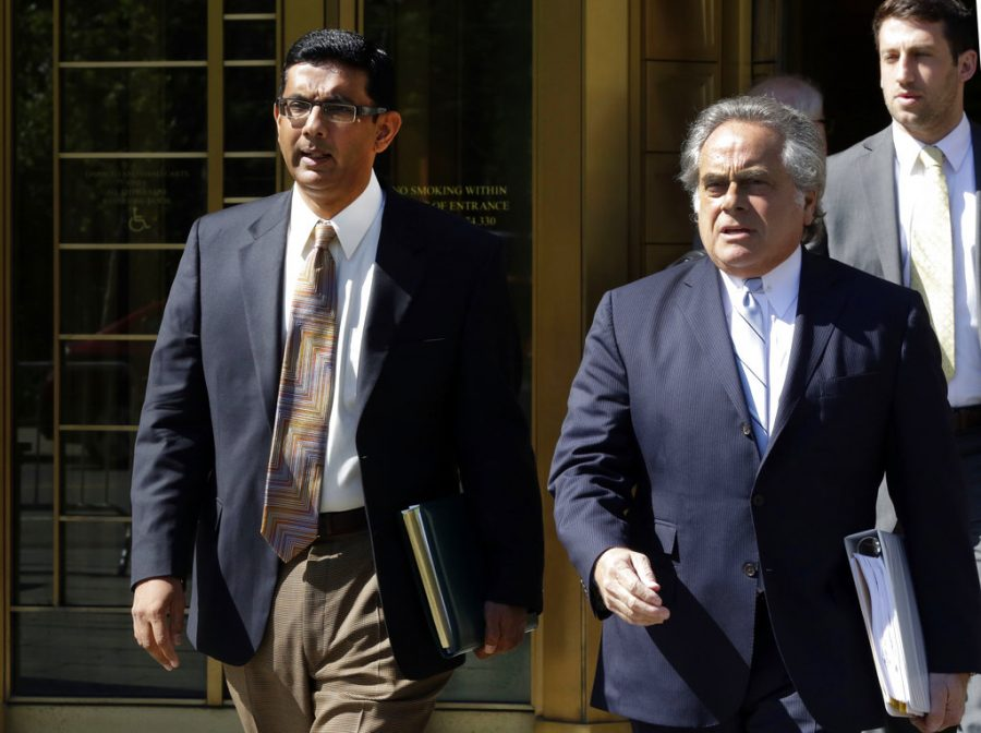 Conservative scholar and filmmaker Dinesh D'Souza, left, leaves federal court in New York accompanied by his lawyer Benjamin Brafman in May 2014. President Donald Trump says he will pardon conservative commentator Dinesh D'Souza who pleaded guilty to campaign finance fraud.