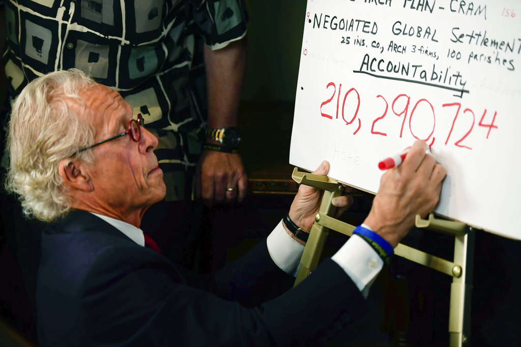 Attorney Jeff Anderson draws a comma while writing down the sum of the settlement reached between the Archdiocese of St. Paul and Minneapolis and clergy sexual abuse victims at his office on  May 31 in St. Paul, Minnesota