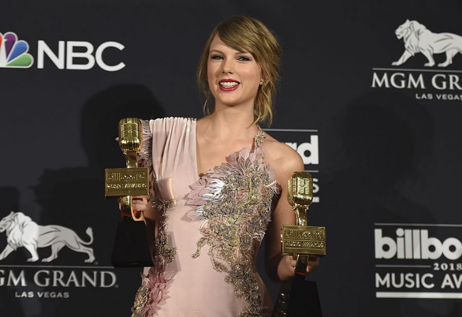 Taylor Swift poses in the press room with the award for top female artist and the award for top selling album for