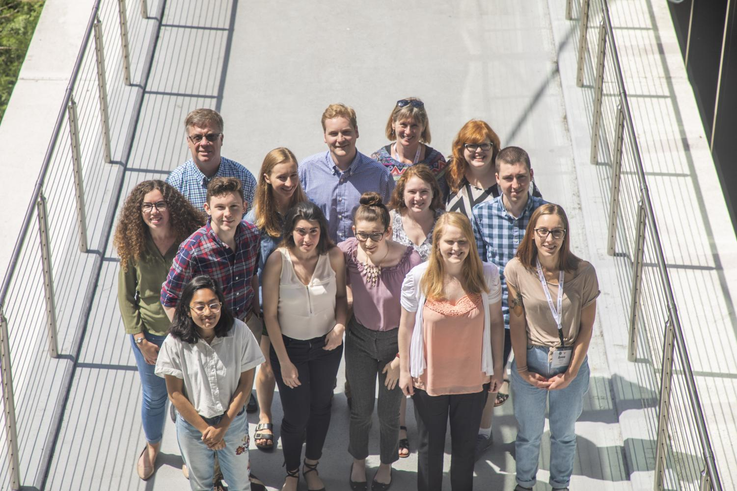 The Dow Jones News Fund interns and faculty members stand on the pedestrian bridge of the Moody College of Communication.