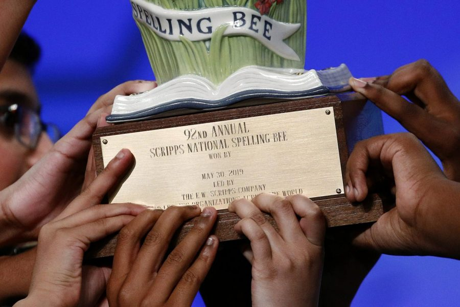 The eight champions of the 92nd Scripps National Spelling Bee grip the competition's trophy, in an unprecedented case where the judges ran out of words.