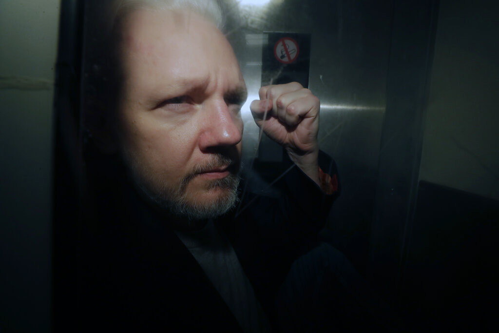 In this May 1, 2019, file photo, WikiLeaks founder Julian Assange puts his fist up as he is taken from court in London.