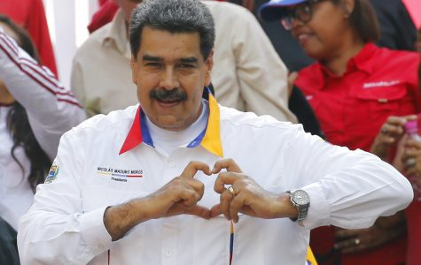 In this May 20, 2109 photo, Venezuela's President Nicolas Maduro flashes a hand-heart symbol to supporters outside Miraflores presidential palace in Caracas, Venezuela. Maduro said Thursday, May 23, 2019, that he is inviting China's Huawei to help set up a 4G network in Venezuela, prompting opposition leader Juan Guaidó to accuse him of having an