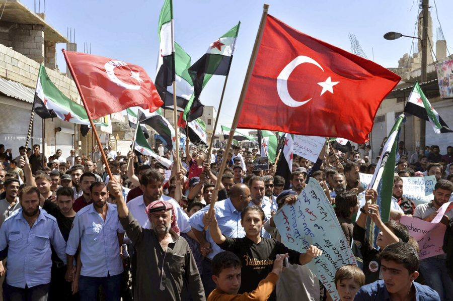 FILE - In this Sept. 14, 2018, file photo, protesters wave revolutionary Syrian and Turkish flags as they attend a demonstration against the Syrian government offensive in Idlib, in Maarat al-Numan, south of Idlib, Syria. The violence raging once again in the northwestern province of Idlib, Syria's last rebel-held bastion, is putting Turkish-Russian relations to the test. (Ugur Can/DHA via AP, File)