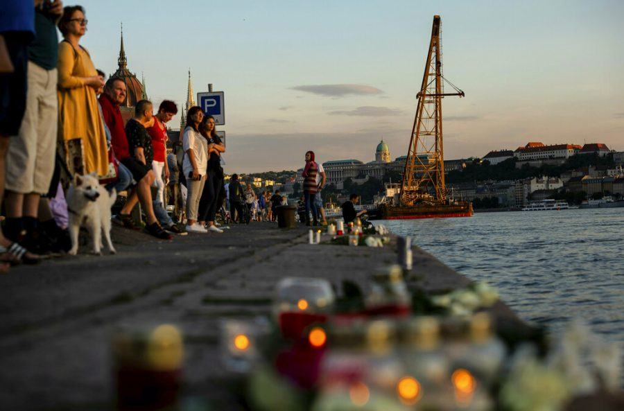 People stand near a river with candles on the sidewalk.
