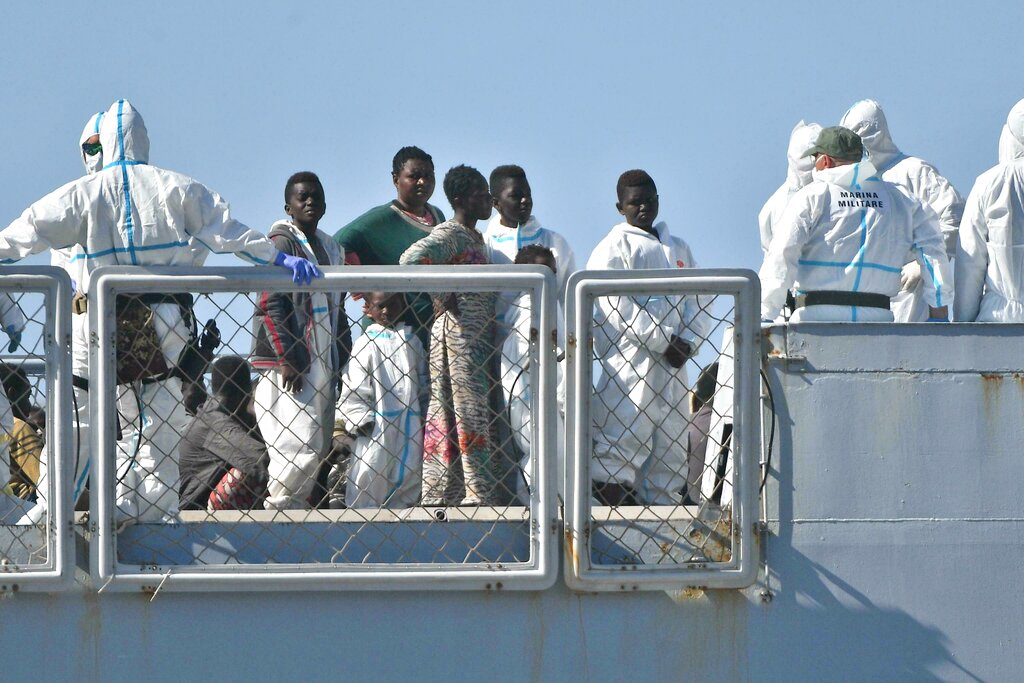 Medical staff help migrants to disembark from the Cigala Fulgosi Italian Navy ship at the harbor in Genoa, Italy, Sunday. An Italian navy ship docked Sunday morning in the northern port city of Genoa carrying 100 migrants who were picked up from the Mediterranean Sea, where the number of migrant crossings has picked up in recent weeks.