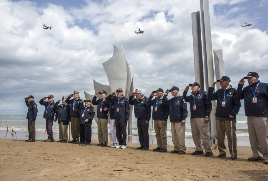 World War II veterans from the United States salute as they pose in front of Les Braves monument at Omaha Beach in Saint-Laurent-sur-Mer, Normandy, France, Monday, June 3, 2019. France is preparing to mark the 75th anniversary of the D-Day invasion which took place on June 6, 1944.