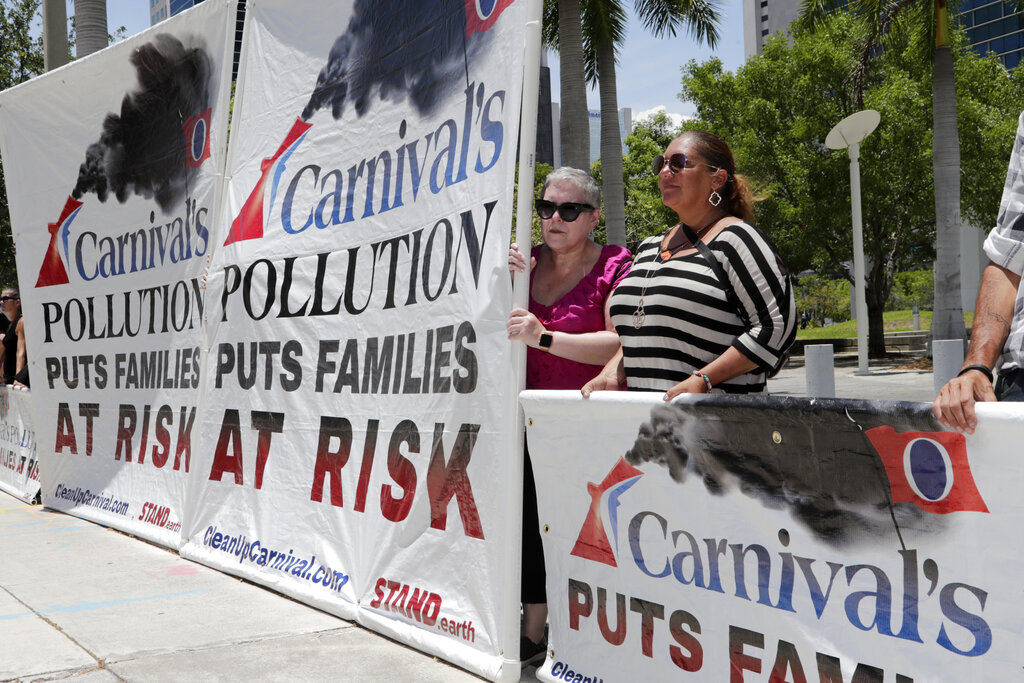 Protestors with Stand.earth hold a banner in opposition to Carnival Corp. outside of federal court, Monday, June 3, in Miami.