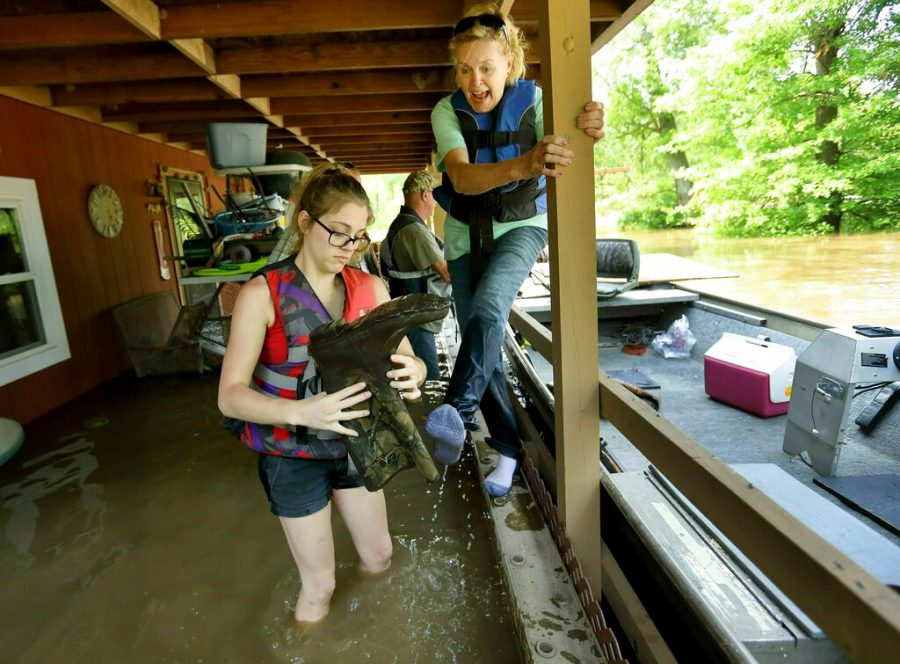 Emily Kientzel empties the water out of her grandmother Joan FitzGerald's boot that is filled with floodwater from the Mississippi River, as they check on the home of a friend outside of Portage des Sioux, Missouri on Sunday. The pair are standing on the second story balcony of the home that has more than a foot of water in it.