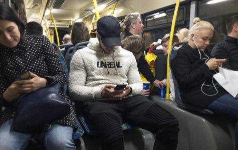 Passengers look at their smartphones on a bus in Moscow, Russia In this photo taken on May 16. Russia's communications regulator says Tinder is now required to provide user data to Russian intelligence agencies.