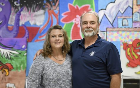 LaNette and David Godfrey pose in front of a colorful wall