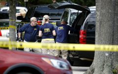 Members of the FBI load equipment into a vehicle as they work in a parking lot outside the municipal building that was the scene of a shooting Saturday in Virginia Beach, Va. DeWayne Craddock, a longtime city employee, opened fire at the building Friday before police shot and killed him, authorities said.