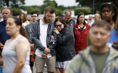 Brittany Myers, right, embraces her husband, Ryan, during a vigil for the Virginia Beach shooting victims
