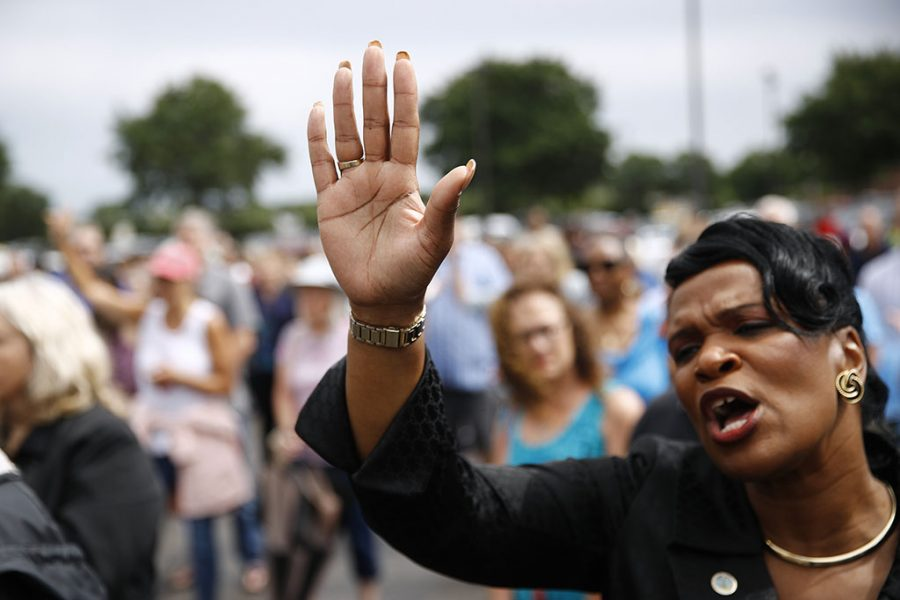 Virginia Beach, Va., council member Sabrina Wooten holds her hand out as she sings during a vigil in response to a fatal shooting at a municipal building in Virginia Beach, Va., June 1. A longtime city employee opened fire at the building Friday before police shot and killed him, authorities said.