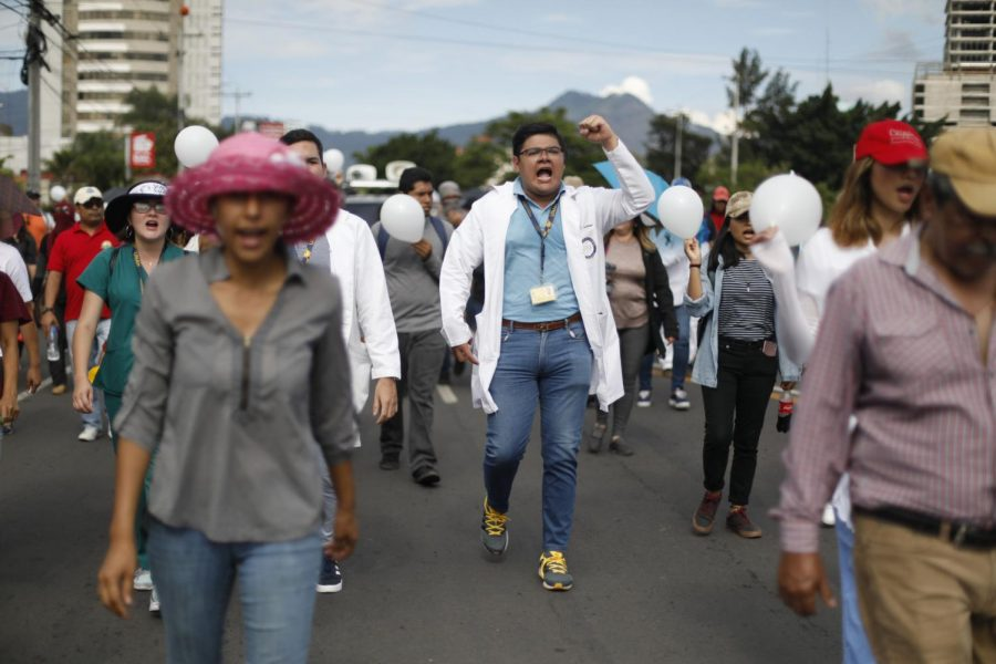 Demonstrators march during a protest against Honduras President Juan Orlando Hernández on Saturday in Tegucigalpa, Honduras. Thousands of doctors and teachers have been marching through the streets of the city for the last three weeks, against presidential decrees they say would lead to massive public sector layoffs.