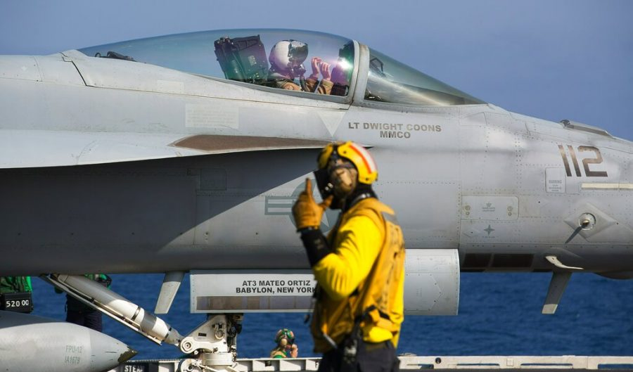 A+crew+member+signals+to+a+pilot+in+an+F%2FA-18+fighter+jet+on+the+deck+of+the+USS+Abraham+Lincoln+aircraft+carrier+in+the+Arabian+Sea.