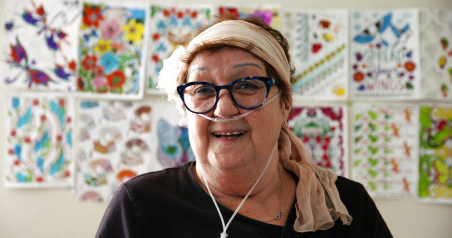 Norma McCorvey, an older woman with short red hair, large blue glasses, a pale peach headscarf, and breathing tubes in her nose stands smiling in front of a wall covered with vibrant drawings of flowers. The image is from her appearance in the documentary,