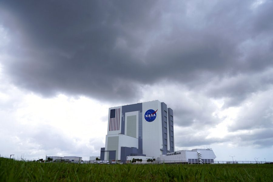 Storm clouds pass over the Vehicle Assembly Building as a SpaceX Falcon 9, with NASA astronauts Doug Hurley and Bob Behnken in the Crew Dragon capsule, sits on Launch Pad 39-A at the Kennedy Space Center in Cape Canaveral, Fla., on May 30, 2020.