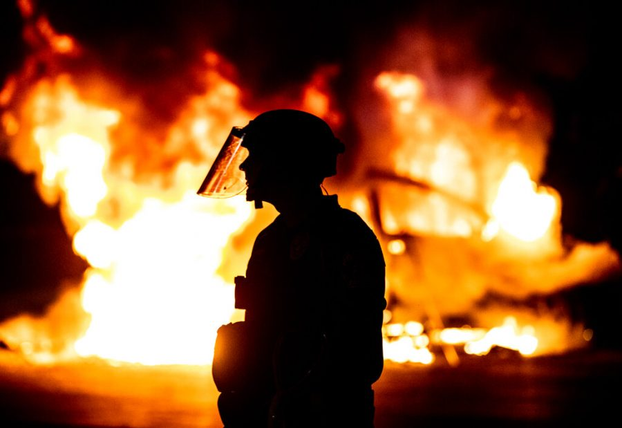 A police officer stands guard as Austin Fire Department puts out a car fire under Interstate 35 in Austin May 30 during a protest over the death of George Floyd, a handcuffed black man who died in Minneapolis police custody.