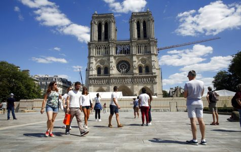 Tourists view the newly repaired Norte Dame cathedral.