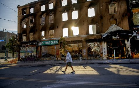 A man walks past a damaged building following overnight protests over the death of George Floyd.