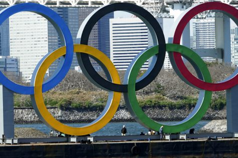 Workers stand at the bottom of the Olympic rings