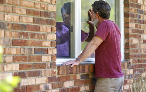 Jack Campise talks with his mother, Beverly Kearns, through her apartment window at the Kimberly Hall North nursing home, May 14, in Windsor, Connecticut. The coronavirus has had no regard for health care quality or ratings as it has swept through nursing homes around the world, killing efficiently even in highly rated care centers. Preliminary research indicates the numbers of nursing home residents testing positive for the coronavirus and dying from COVID-19 are linked to location and population density — not care quality ratings.