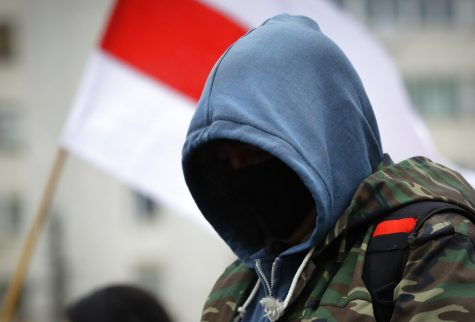 A man with a hood over his face protests in Belarus.
