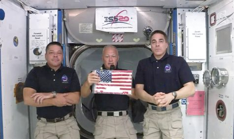 Astronauts in the space station hold a small American flag