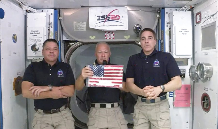 Astronauts+in+the+space+station+hold+a+small+American+flag