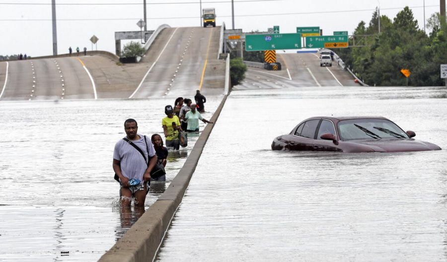 Evacuees wade through floodwaters from Tropical Storm Harvey on a section of Interstate 610 in Houston on Aug. 27, 2017.