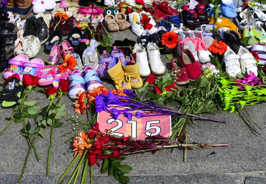 Flowers, children's shoes and other items rest at a memorial at the Eternal flame on Parliament Hill in Ottawa on Tuesday, June 1, 2021, in recognition of discovery of children's remains at the site of a former residential school in Kamloops, British Columbia. (Sean Kilpatrick/The Canadian Press via AP)