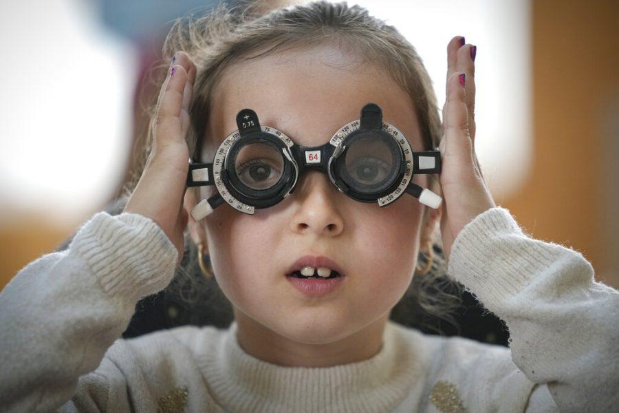 Girl adjusts glasses during eyesight examination